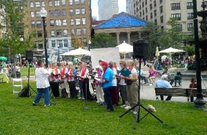 15 singers in white shirts and red choir stoles gathered outdoors at the Boston Common to sing for peace