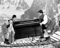 Laurel and Hardy moving a piano over a narrow footbridge in the Alps