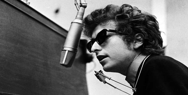 Bob Dylan singing at a mic, neck forward with harmonica attached to his neck